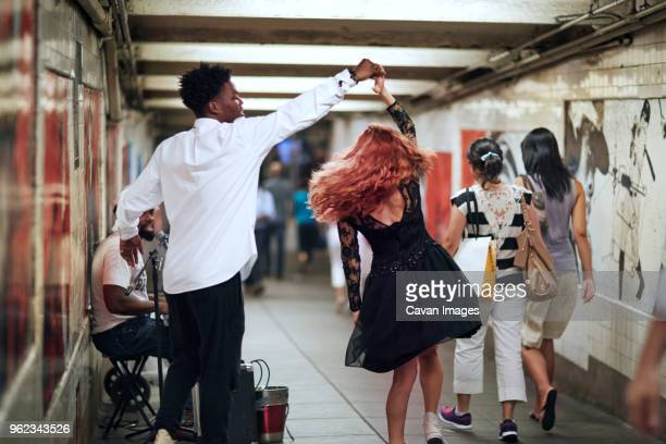happy couple dancing while street musician singing in subway - busker stock pictures, royalty-free photos & images