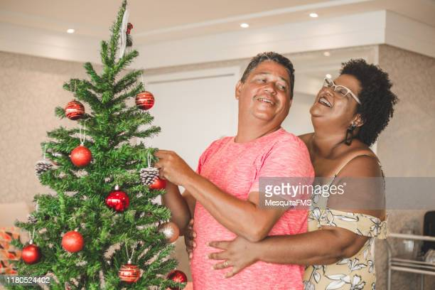 happy couple decorating the christmas tree - models in stockings stock pictures, royalty-free photos & images