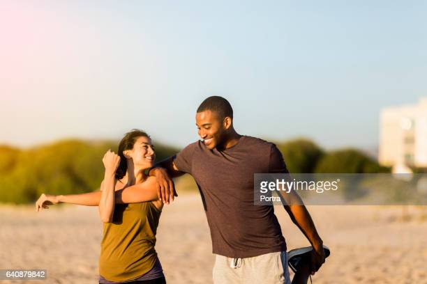 happy couple doing stretching exercises at beach - black men feet stock photos and pictures