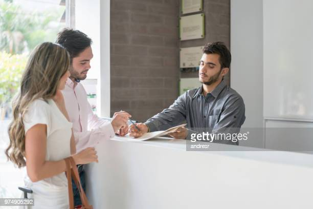 happy couple doing the check-in at a hotel - making a reservation stock photos and pictures