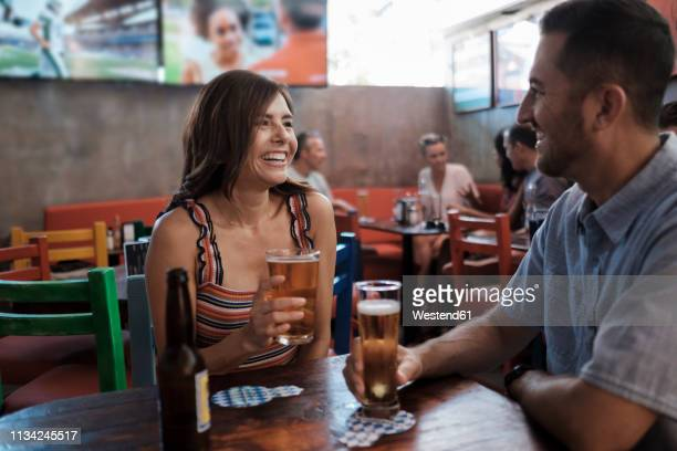 happy couple drinking beer in a bar - daten stockfoto's en -beelden