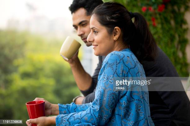 happy couple drinking coffee at balcony - married stock pictures, royalty-free photos & images