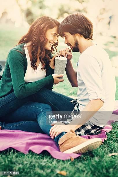 Happy couple drinking from one cup