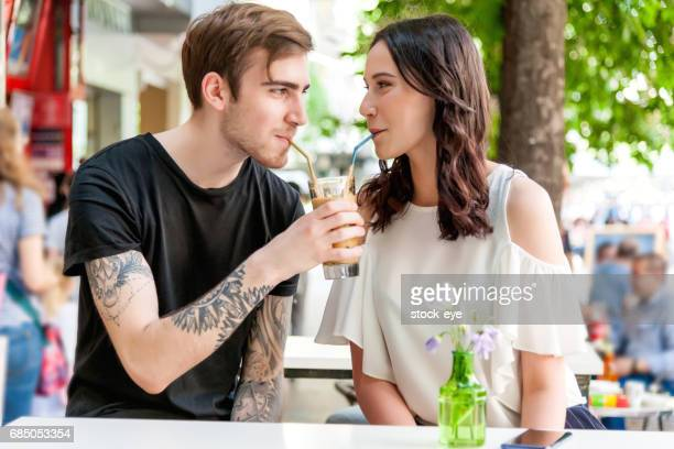 happy couple drinking from one cup - milkshake imagens e fotografias de stock