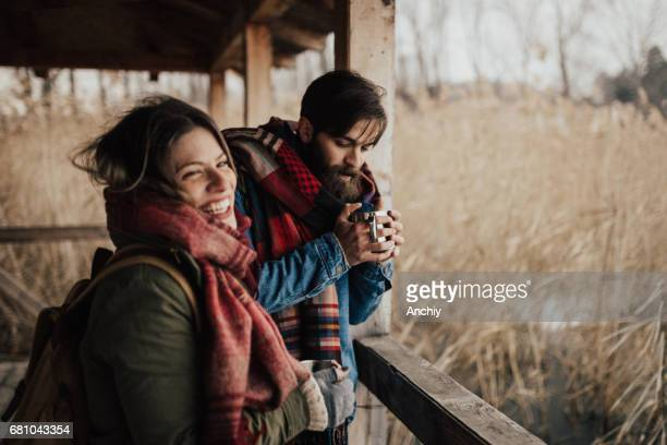 pareja feliz de beber té caliente en un día frío - casita de campo fotografías e imágenes de stock