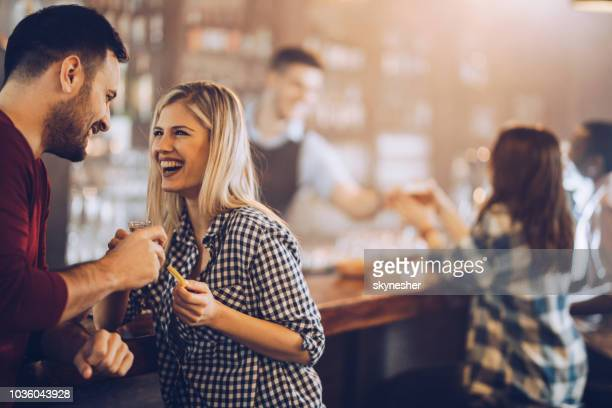 happy couple drinking tequila shots during their night out in a bar. - flirting stock pictures, royalty-free photos & images