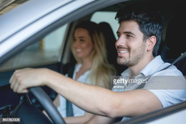 happy couple driving a car at the dealership - test drive stock pictures, royalty-free photos & images