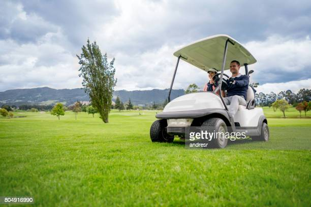 Happy couple driving a golf cart at the course