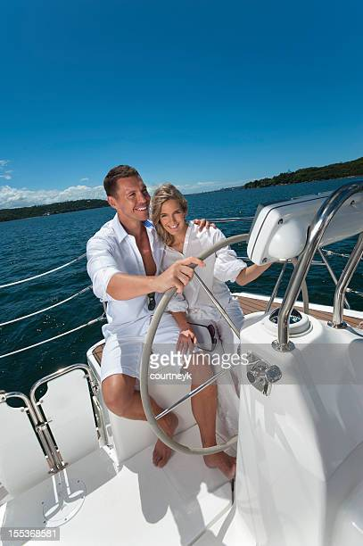 Happy couple driving a sailboat with clear sky