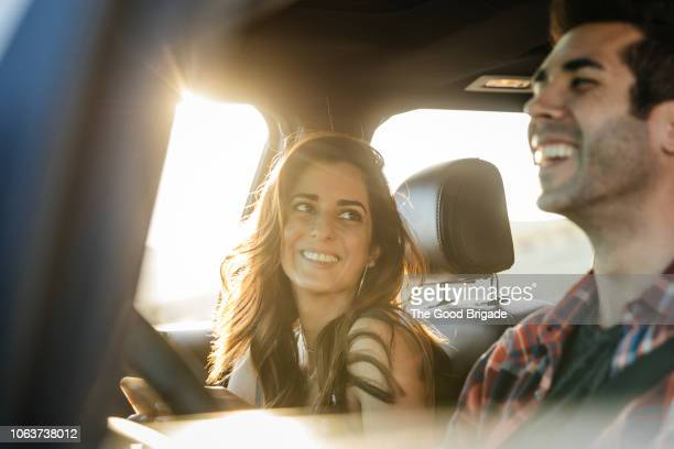 happy couple driving in car on road trip - heterosexuelles paar stock-fotos und bilder