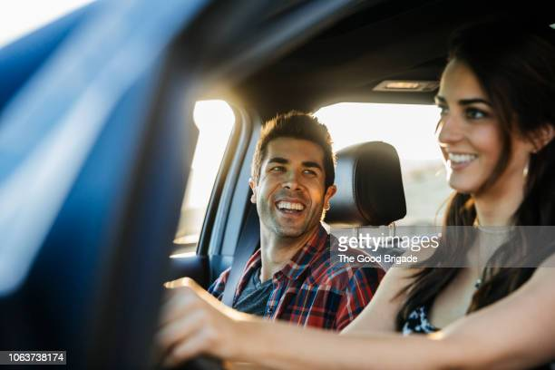 happy couple driving in car on road trip - friends inside car stock photos and pictures