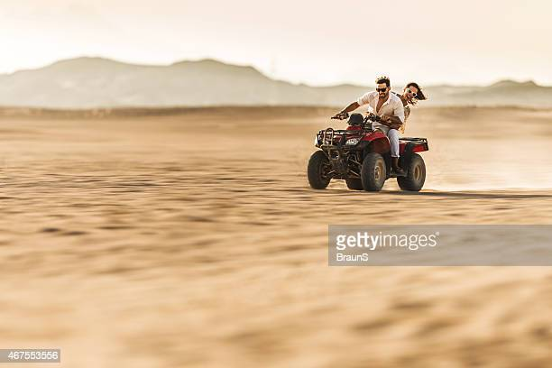 Happy couple driving quad bike in the desert.