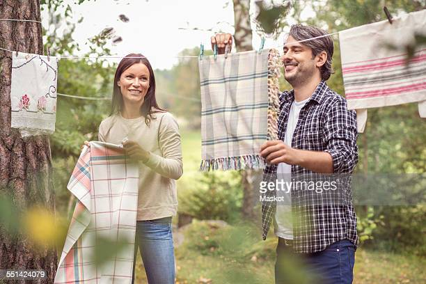 Happy couple drying laundry in yard