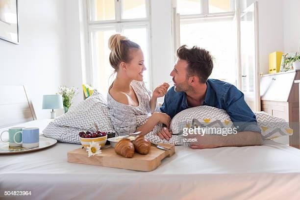 Glückliches Paar Essen Frühstück im Bett zu Hause fühlen