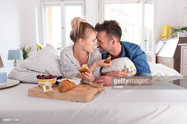 Happy couple eating breakfast in the bed