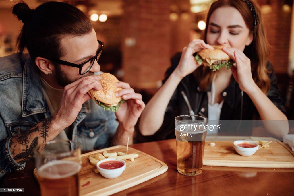 Casal feliz comendo hambúrgueres em uma noite de data : Foto de stock