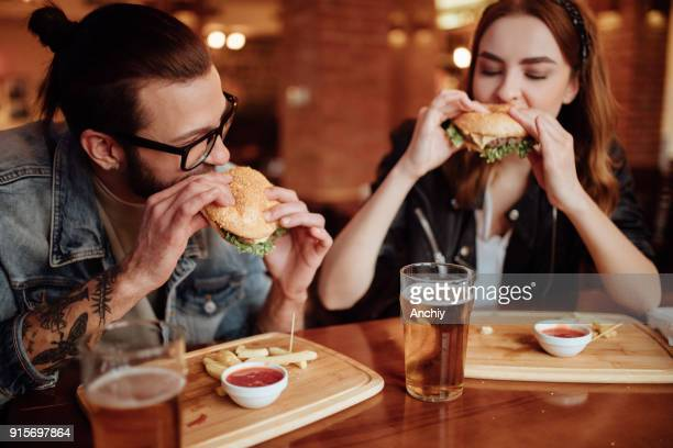 Happy couple eating burgers on a date night