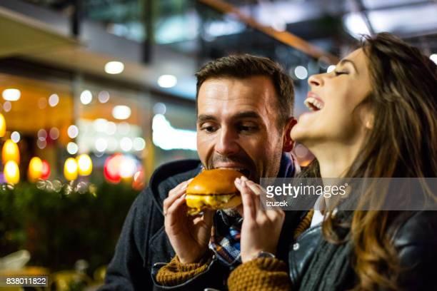 glückliches paar fastfood zusammen - izusek stock-fotos und bilder