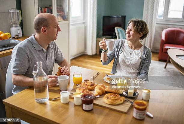 Happy couple eating french breakfast at home