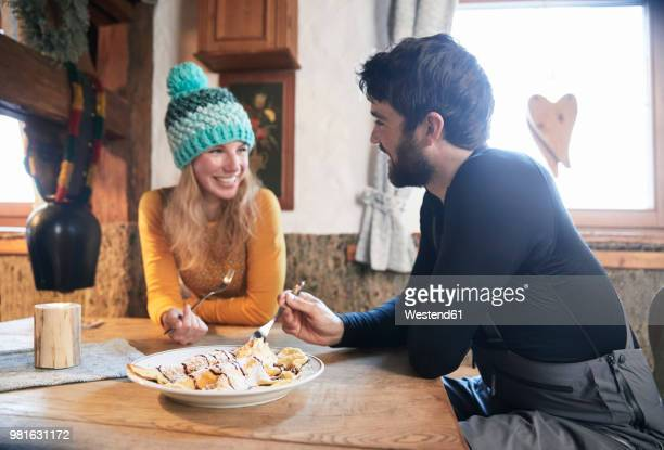 Happy couple eating in rustic mountain hut
