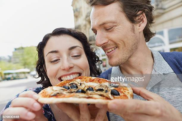 Happy couple eating pizza outdoors