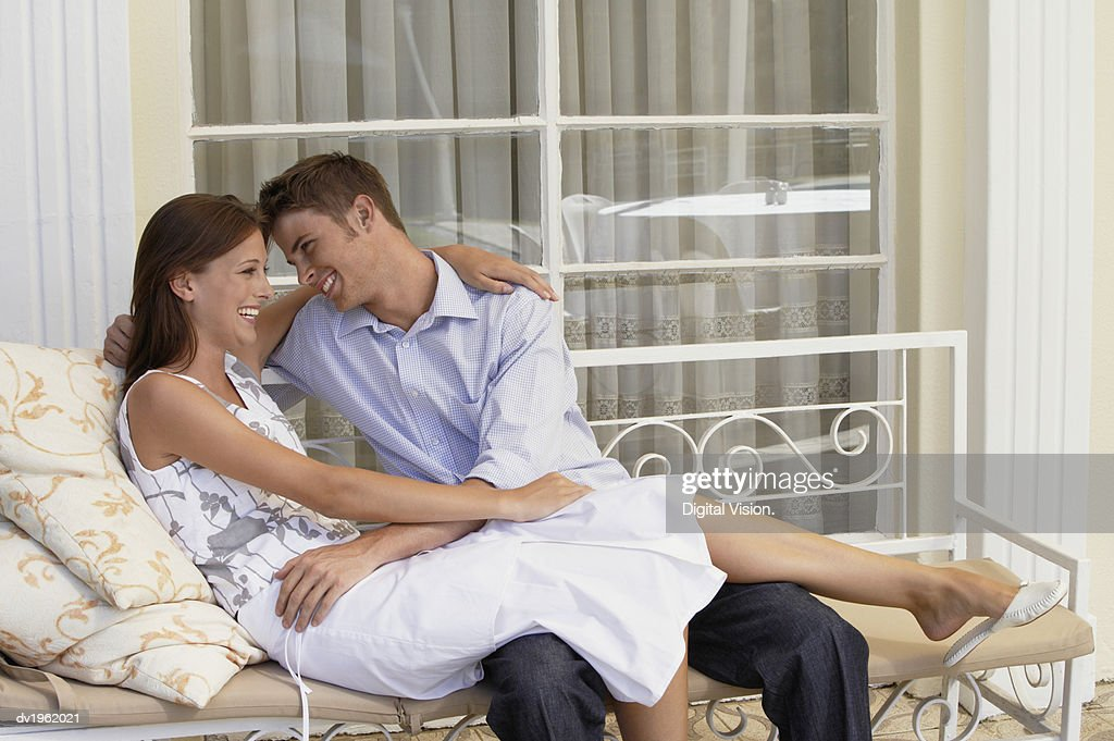 Happy Couple Embrace on a Bench on a Porch : Stock Photo