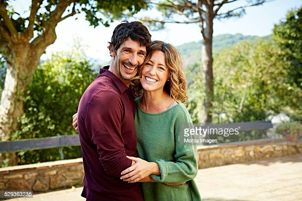 happy couple embracing in park - 40 49 years stock pictures, royalty-free photos & images