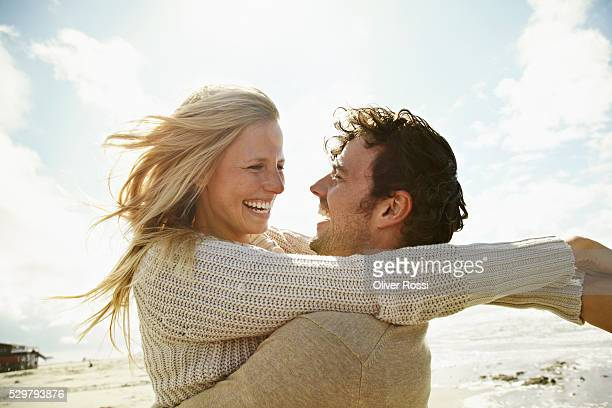 happy couple embracing on beach - mid adult couple stock pictures, royalty-free photos & images