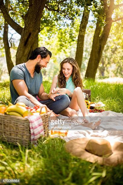 Heureux couple appréciant un pique-nique dans un parc d'été