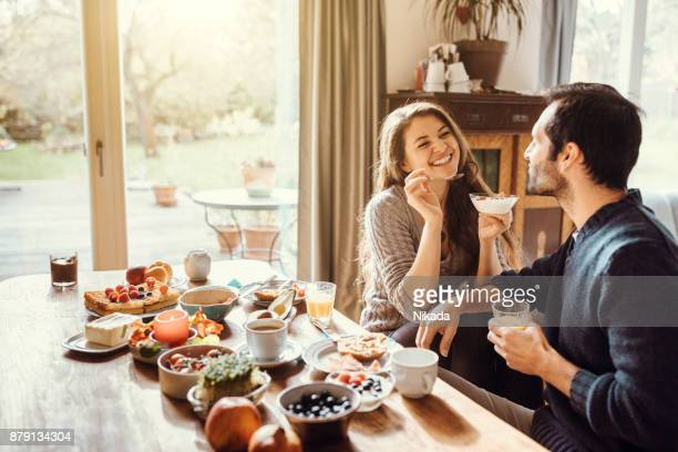 happy couple enjoying breakfast together - sala da pranzo foto e immagini stock