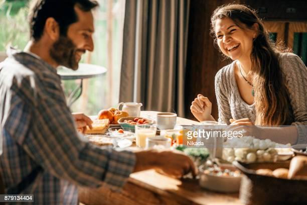 casal feliz, desfrutar de pequeno-almoço juntos - mesa de jantar - fotografias e filmes do acervo