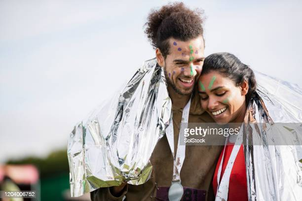 happy couple enjoying end of charity run together - medallist stock pictures, royalty-free photos & images