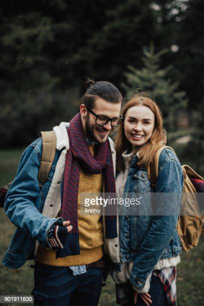 Happy couple enjoying hiking in the forest on a snowy day