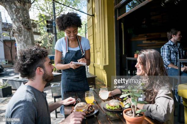 happy couple enjoying lunch on a lovely day and ordering something to the waitress - waitress stock pictures, royalty-free photos & images