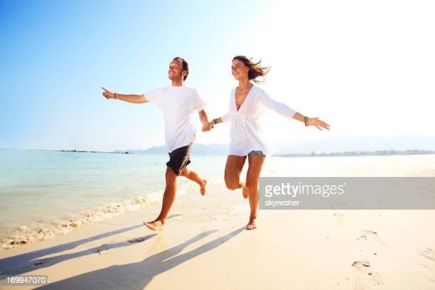 Glückliches Paar genießen Joggen und Hände halten am Strand.
