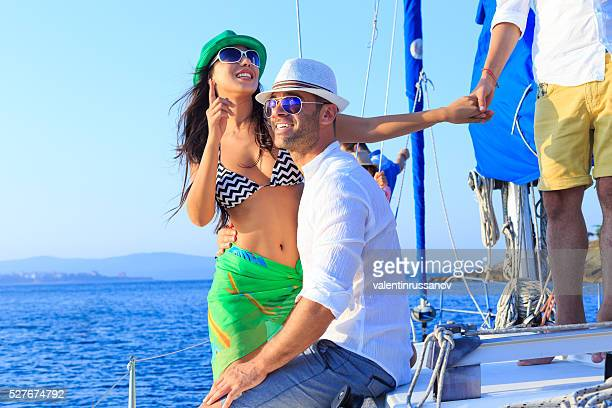 Happy couple enjoying sailboat trip
