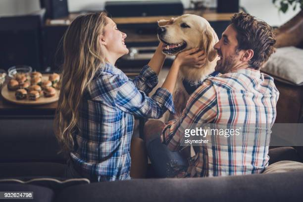 Happy couple enjoying with their golden retriever in the living room.