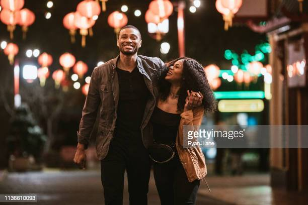 happy couple exploring chinatown in downtown los angeles at night - nightlife stock pictures, royalty-free photos & images