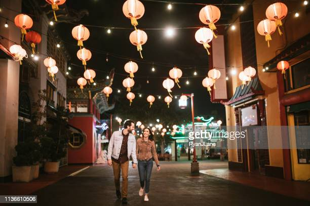 happy couple exploring chinatown in downtown los angeles at night - chinatown stock pictures, royalty-free photos & images
