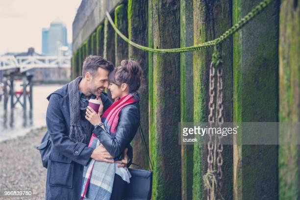 gelukkige paar flirten op de oever in de stad - izusek stockfoto's en -beelden