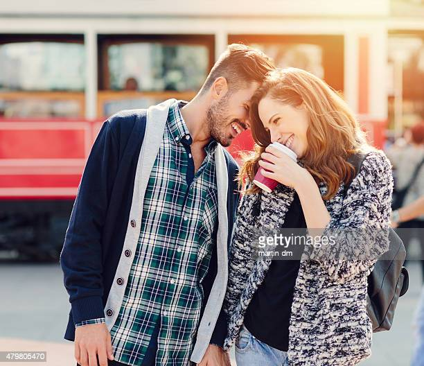 happy couple flirting outside - verlegen stockfoto's en -beelden