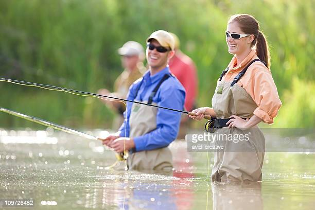 happy couple fly fishing together - fly fishing stock photos and pictures