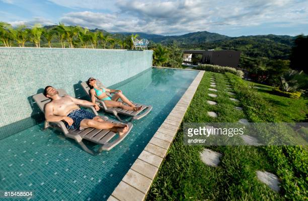 happy couple getting a tan in the swimming pool - template_talk:south_carolina stock pictures, royalty-free photos & images