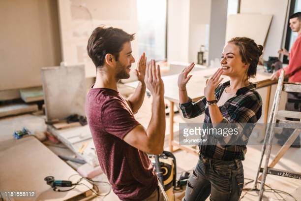 happy couple giving each other high-five at their renovating apartment. - rebuilding stock pictures, royalty-free photos & images