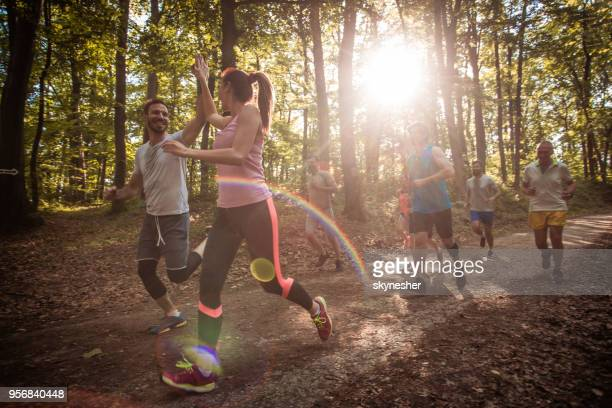 happy couple giving high-five while running marathon race in nature. - cross country running stock pictures, royalty-free photos & images