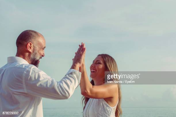 happy couple giving high-five while standing at beach against clear sky - paisajes de puerto rico fotografías e imágenes de stock