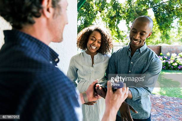 Happy couple giving wine bottle to man at home