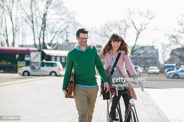 Happy couple going home together, woman riding bicycle