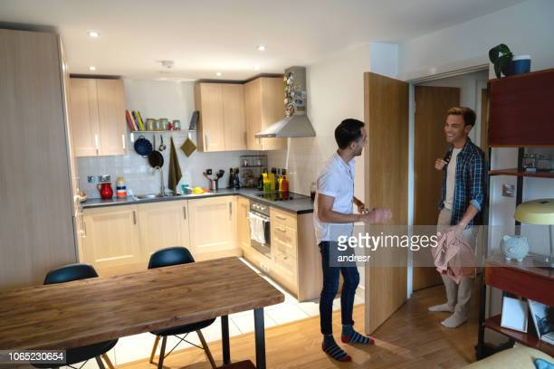happy couple greeting at the door at home - roommate stock pictures, royalty-free photos & images