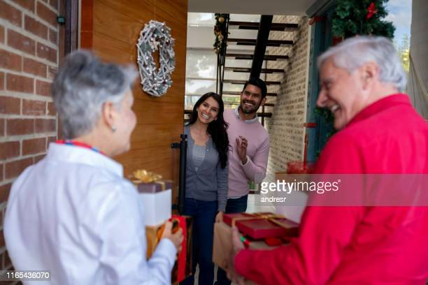 happy couple greeting their parents arriving at home for christmas - hello december stock pictures, royalty-free photos & images